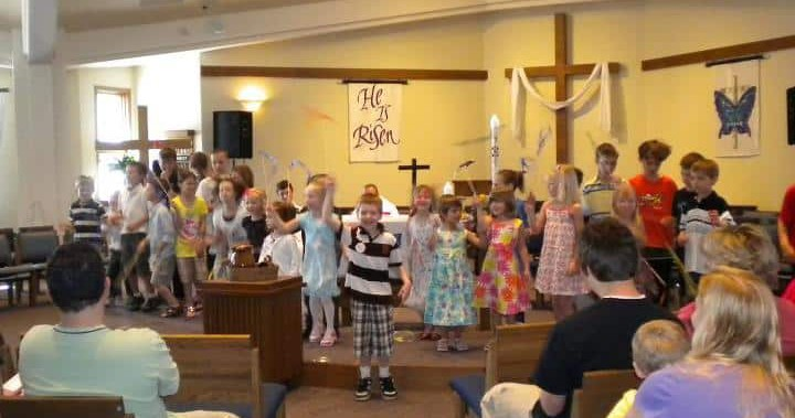 kids holding up pictures they made in sunday school.